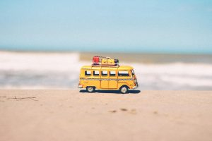 Yellow van on the beach with suitcases on the top.