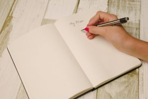 A person making a plan in a notebook, possibly about moving and packing fragile items to Colorado.