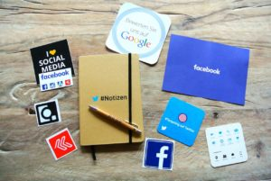 notebook surounded with signs of social media