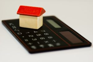 Calculator with model of house on it