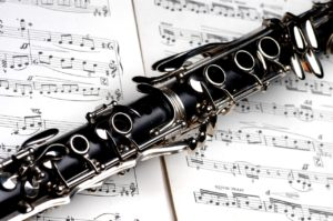 A clarinet on top of some musical notes.