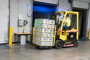 A man riding on a yellow forklift moving the more fragile things in order to prevent property damage when moving out.