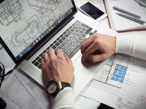 A man looking at blueprints related to building an office in an apartment.