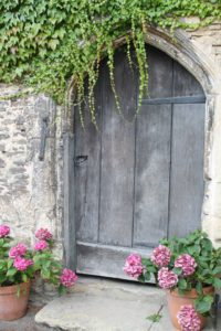 Wooden door in a stone wall which is not a good choice when buying a quality exterior door.
