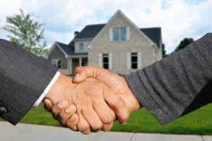 A person shaking hands after buying real estate in New Jersey