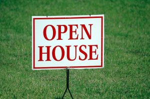 AN open house sign on the grass.