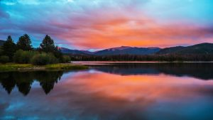 Sunset, mountains, and the lake you will enjoy after buying a property in Summit County.