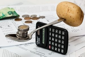 A calculator with a spoon on it that is holding a pile of coins on one and a potato on the other side.