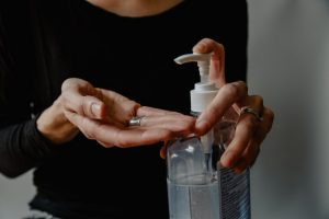 A woman sanitizing her hands because of the pandemic.