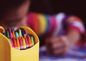 A kid coloring with crayons.