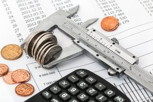 A calculator and some coins squeezed together as the finances are an important factor in Denver vs. Trenton comparison.