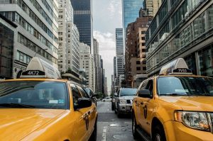 Two yellow cabs on a boulevards  with some buildings on the background.
